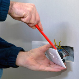 electrician changing a UK power socket